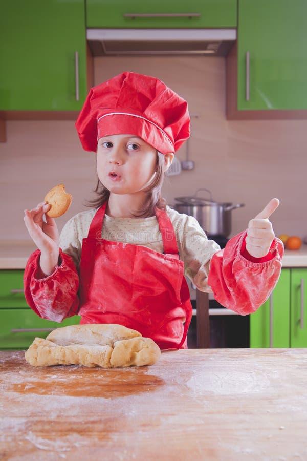 Милая девушка маленького ребенка с тортом и пробовать удерживания шляпы шеф-повара его стоковые изображения rf