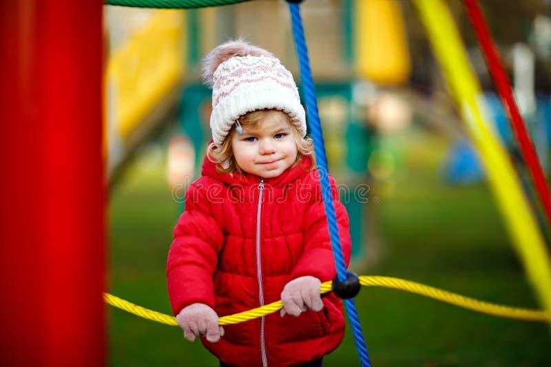 Милая девушка малыша имея потеху на спортивной площадке Счастливый здоровый маленький ребенок взбираясь, отбрасывая и сползая на  стоковое изображение rf