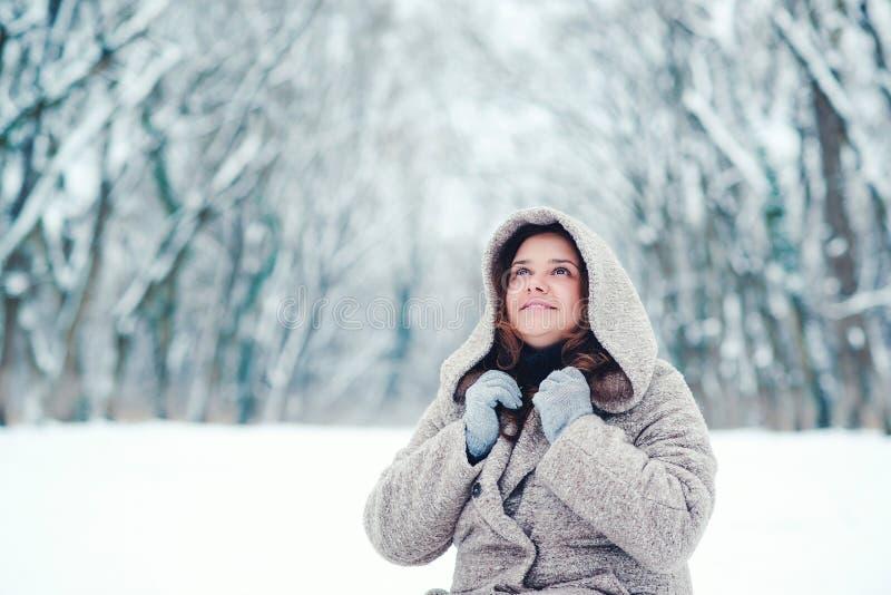 Милая девушка мечтая в парке зимы Время зимнего отдыха и рождества Молодая женщина в пальто идя в парк зимы Усмехаясь девушка d стоковая фотография rf