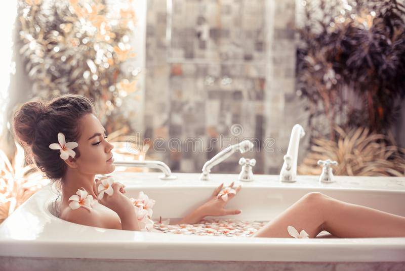 Милая девушка наслаждаясь ванной с цветками plumeria тропическими r Спа ослабляет Женщина крупного плана красивая купая с стоковое фото rf