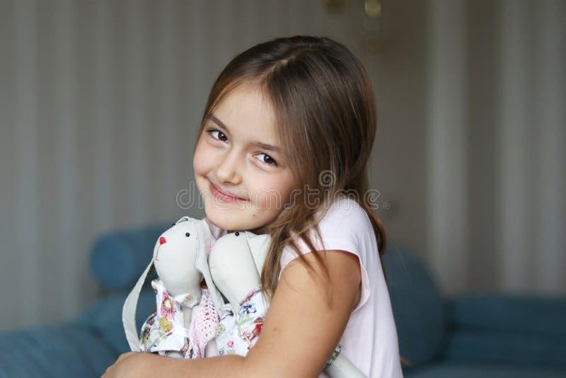 Милая девушка обнимая кроликов зайчика стоковое изображение rf