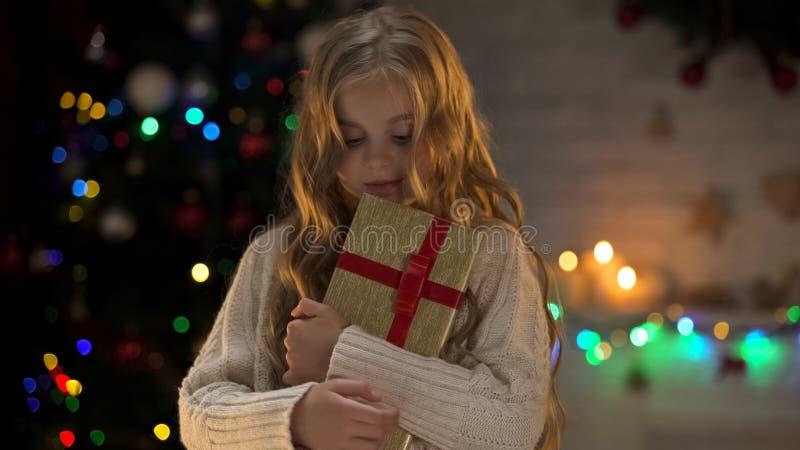 Милая девушка обнимая подарочную коробку, длинный ожиданный подарок на рождество, сказку зимы стоковое изображение rf