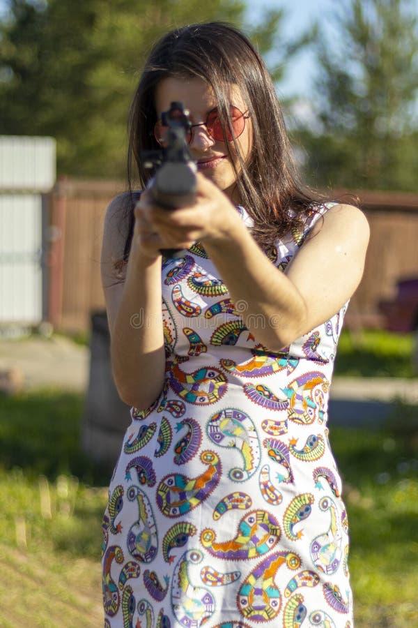 Милая девушка охотника направляя с охотиться винтовка в наружной древесине Штуцер с оптически-видимостью стоковые фото