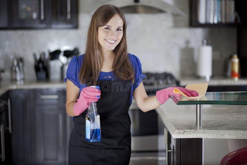 Милая девушка очищая кухню стоковое изображение rf