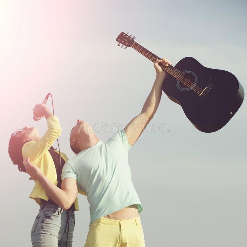 Милая девушка, певица, поя к mic с красивым человеком, гитарист, стоковое фото rf