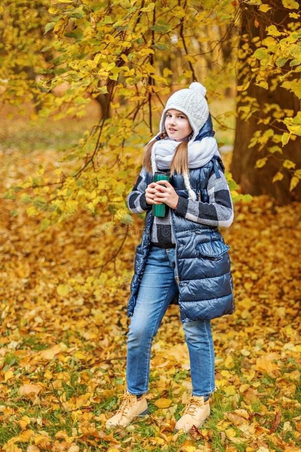 Милая девушка подростка в белой шляпе и объемном шарфе держа thermos с чаем в парке осени стоковое фото rf