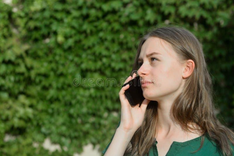 Милая девушка подростка говоря и усмехаясь на мобильном телефоне outdoors r стоковые изображения rf