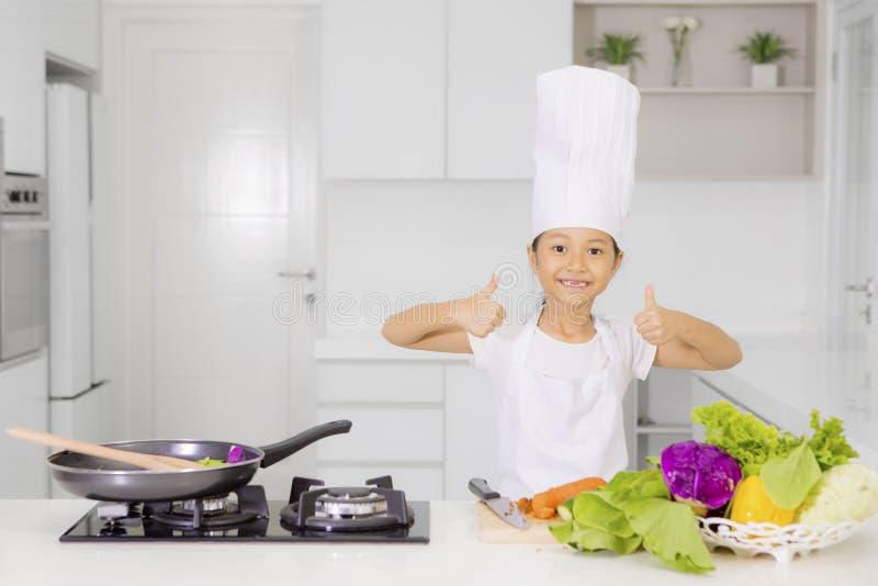Милая девушка показывая большие пальцы руки вверх в кухне стоковые фотографии rf