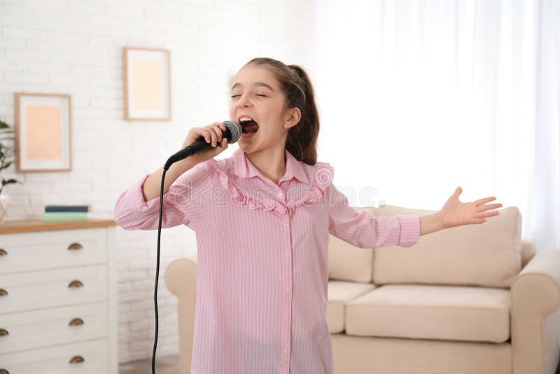 Милая девушка поя в микрофоне стоковое фото rf