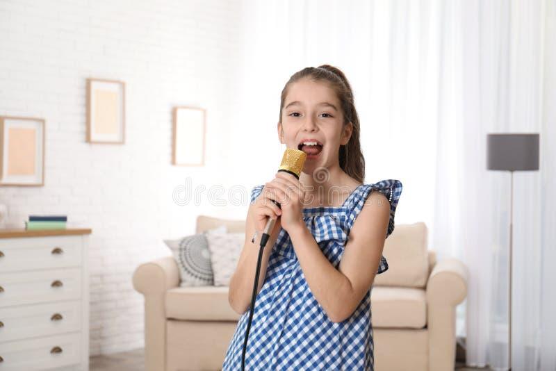 Милая девушка поя в микрофоне стоковое изображение