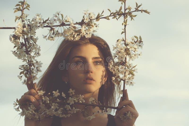 Милая девушка представляя во флористической рамке на голубом небе стоковая фотография