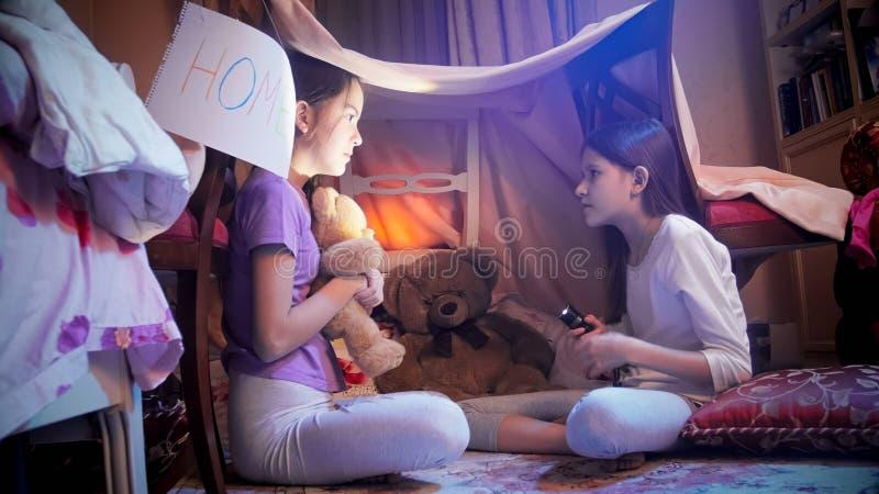 Милая девушка при электрофонарь говоря рассказ к ее вспугнутому другу в шатре на спальне стоковое изображение rf