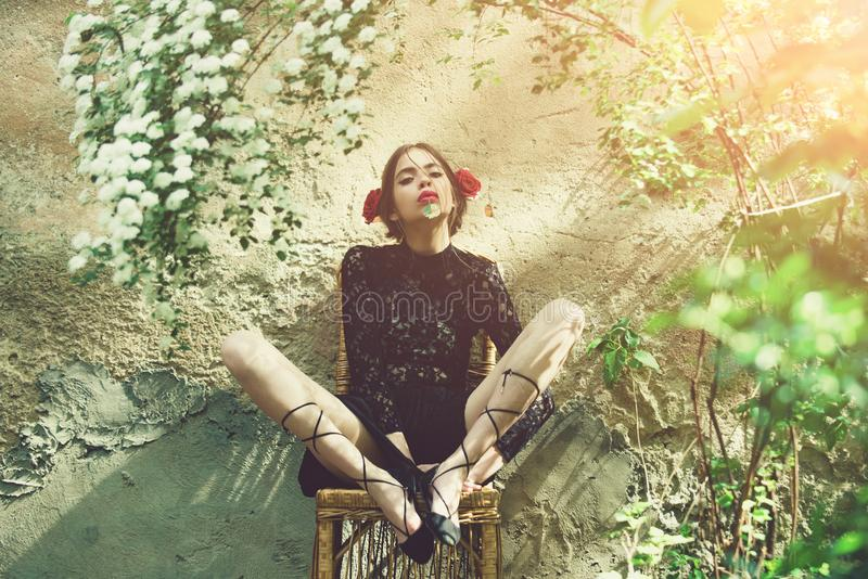 Милая девушка связывая шнурки ботинка на плетеном стуле на солнечный день стоковое фото