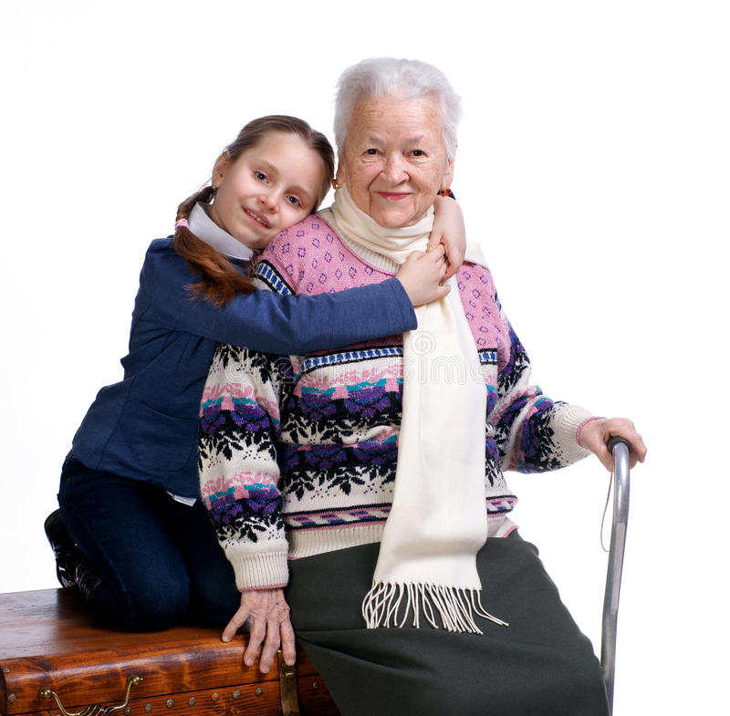 Милая девушка сидя на коробке и обнимая ее бабушку стоковая фотография