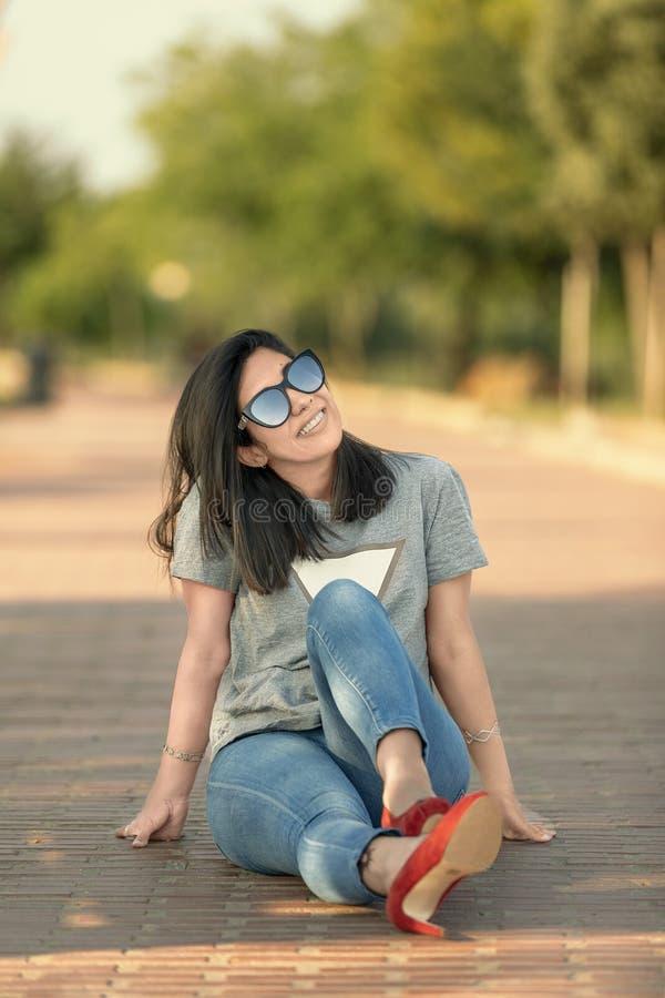 Милая девушка сидя на поле смотря вверх стоковые фотографии rf