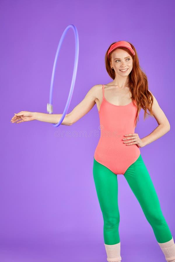 Милая девушка студента с длинными курчавыми красными волосами делая тренировки с обручем hula в классе фитнеса стоковое фото rf
