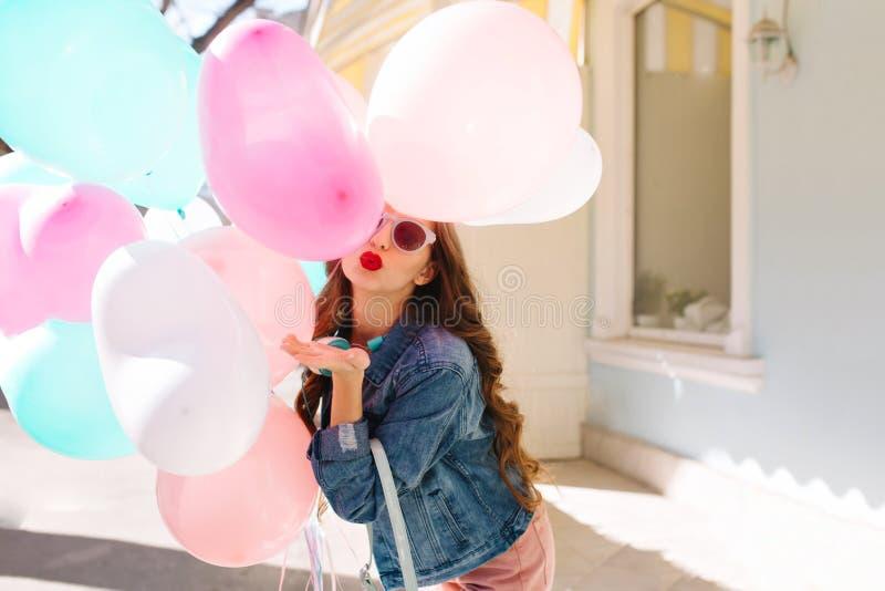 Милая девушка с длинным вьющиеся волосы в солнечных очках прячет за пуком воздушных шаров и отправляет поцелуй воздуха Портрет  стоковые изображения rf