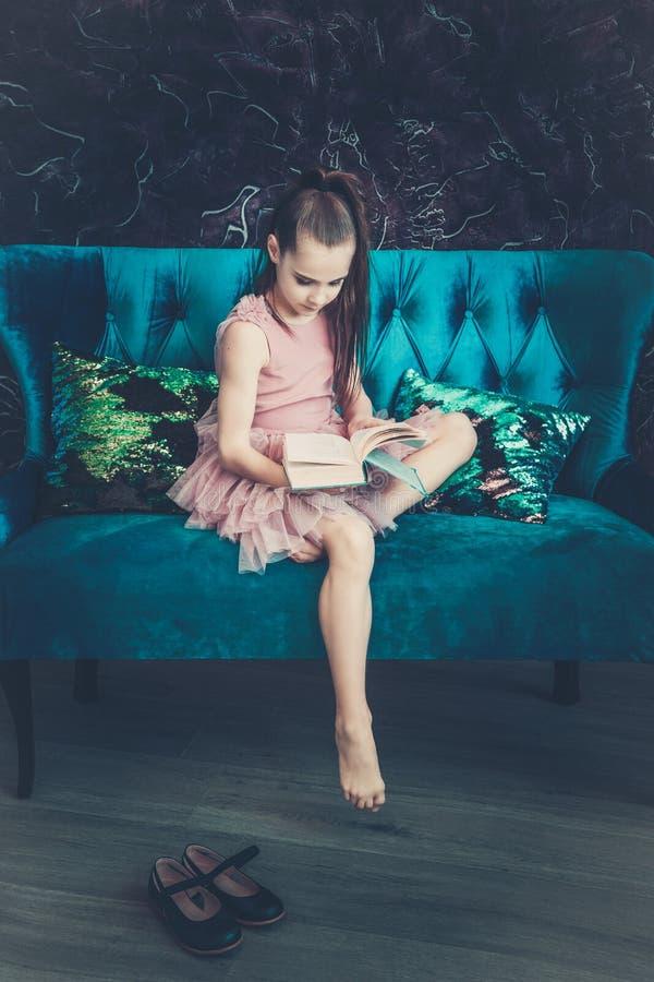 Милая девушка с каштановыми волосами в розовом платье сидя на голубой софе и читая книгу стоковая фотография