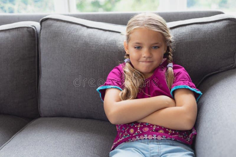 Милая девушка с рукой пересекла сидеть на софе в удобном доме стоковая фотография