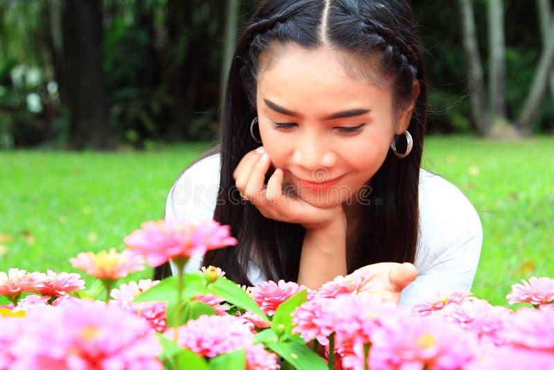 Милая девушка с цветками, платье кавказской женщины нося белое ослабляя стоковое фото