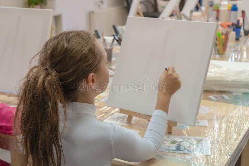 Милая девушка с щеткой в руке Творческий предназначенный для подростков практикуя рисовать в художественном училище Интерьер худо стоковое изображение