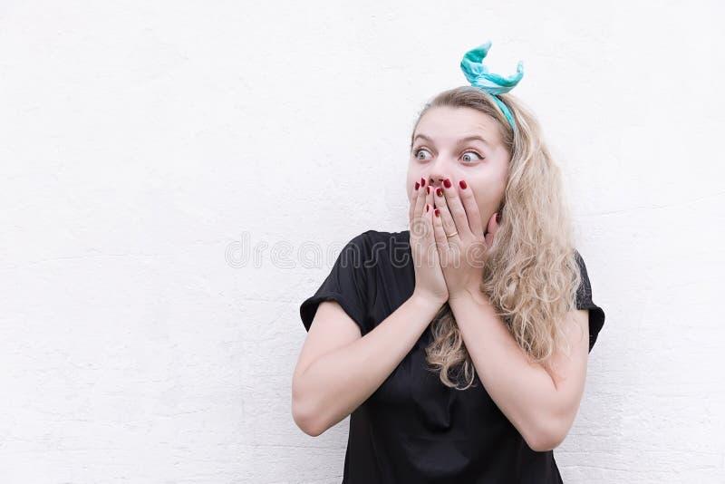 Милая девушка удивленная в закрывать рот, ладони стоковое изображение rf