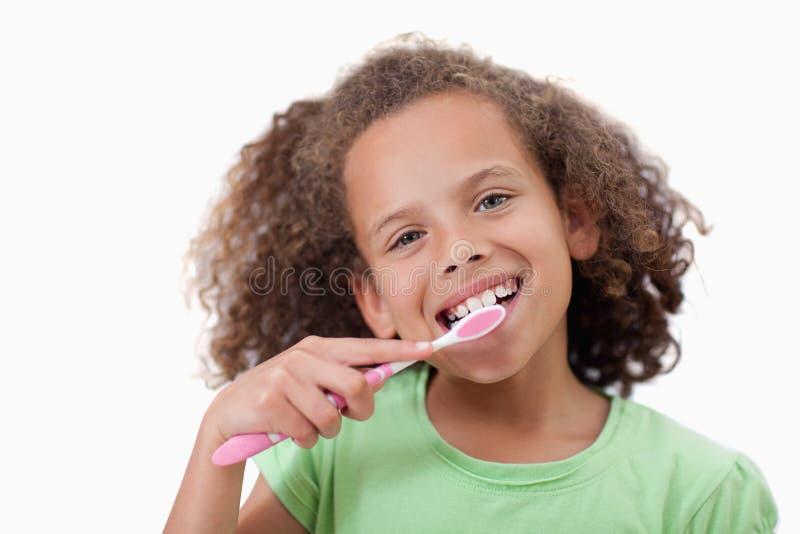 Милая девушка чистя ее зубы щеткой стоковая фотография rf