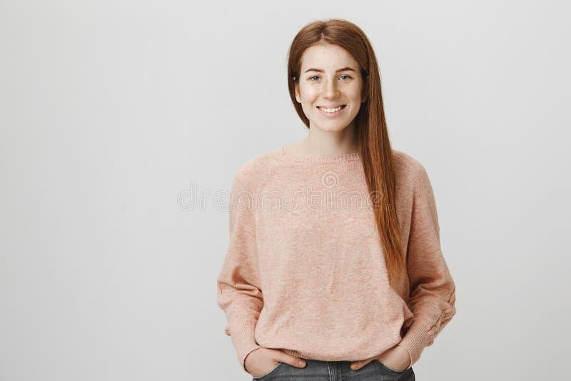 Милая девушка redhead при очаровательная улыбка и веснушки держа руки в карманн, стоя над серой предпосылкой Застенчивое мечтател стоковая фотография