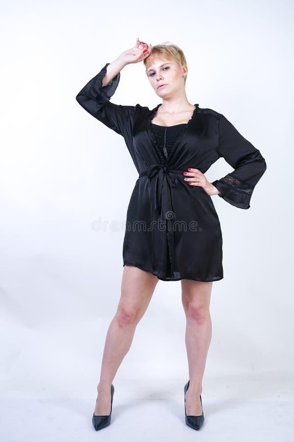 Милая добавочная женщина размера с короткими волосами и пухлое curvy тело нося ретро нижнее белье bodysuit и представляя на белом стоковое изображение