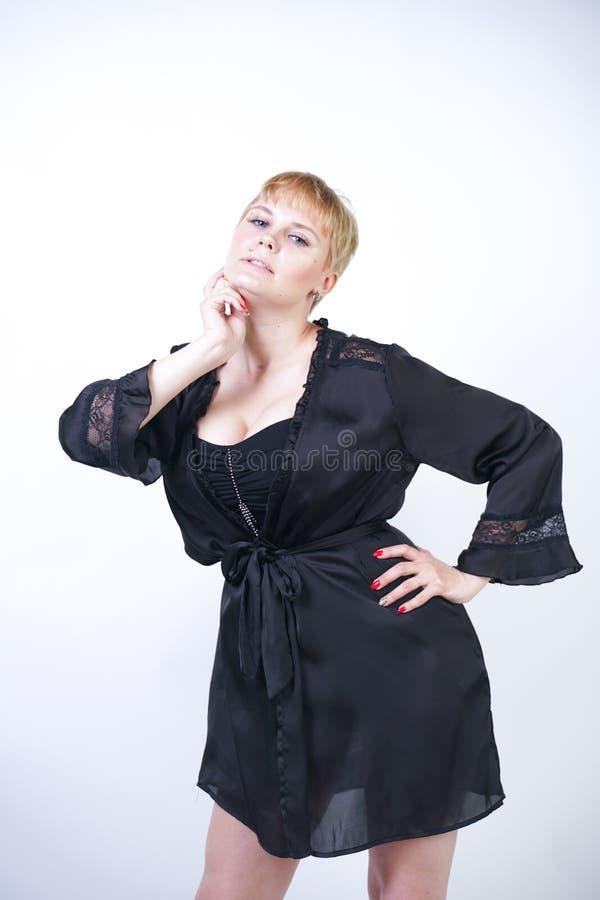 Милая добавочная женщина размера с короткими волосами и пухлое curvy тело нося ретро нижнее белье bodysuit и представляя на белом стоковое фото rf