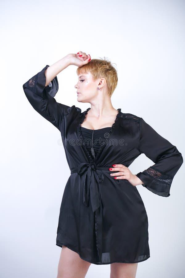 Милая добавочная женщина размера с короткими волосами и пухлое curvy тело нося ретро нижнее белье bodysuit и представляя на белом стоковые фотографии rf
