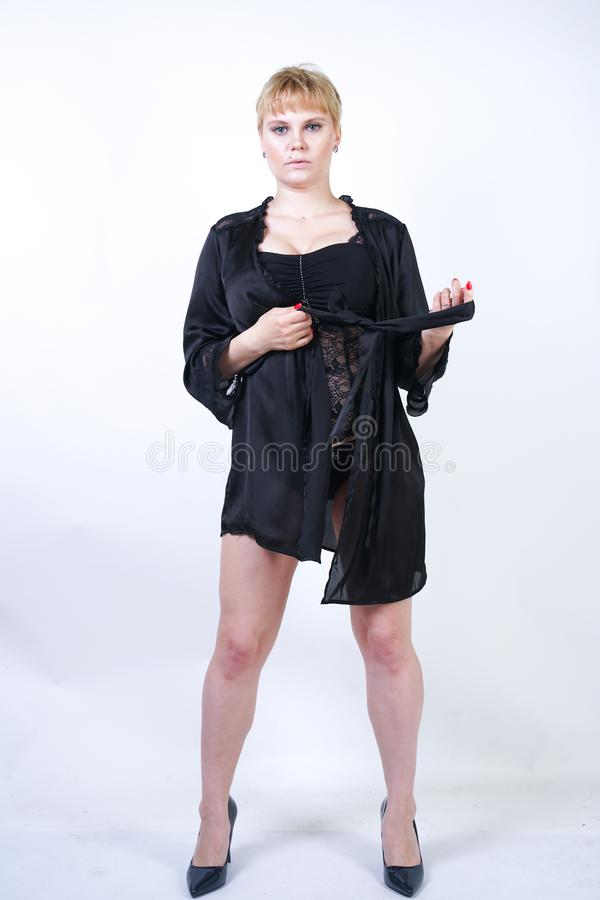 Милая добавочная женщина размера с короткими волосами и пухлое curvy тело нося ретро нижнее белье bodysuit и представляя на белом стоковые изображения