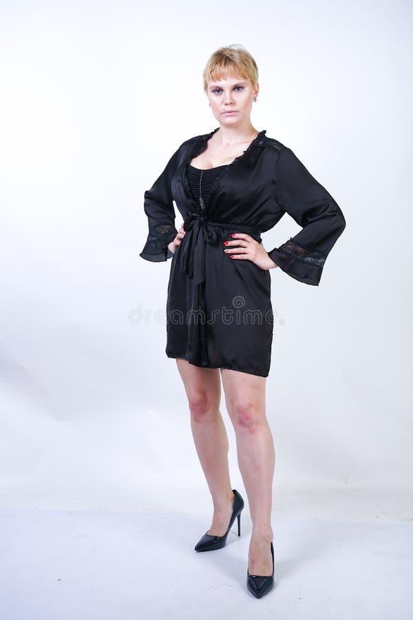 Милая добавочная женщина размера с короткими волосами и пухлое curvy тело нося ретро нижнее белье bodysuit и представляя на белом стоковое изображение rf