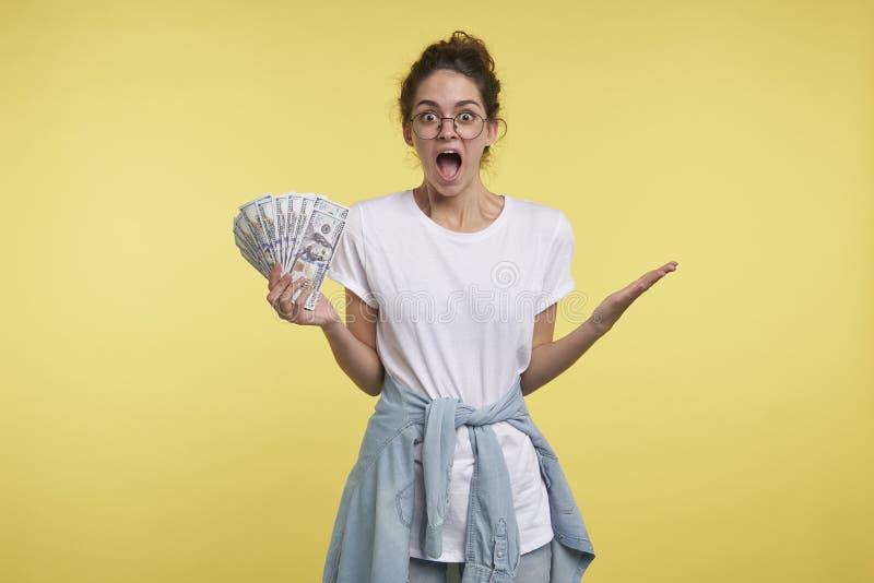 Милая женщина брюнета держит серии наличных денег в руке и дурак клекотов счастья, одел случайное стоковые изображения rf