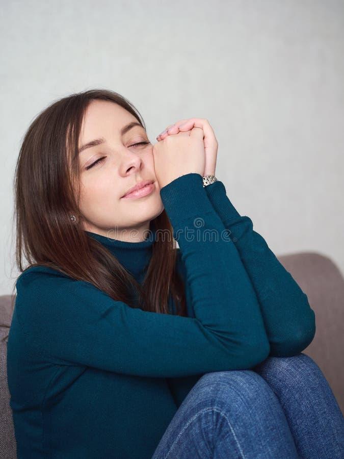 Милая женщина брюнета с великолепными глазами и прелестная улыбка в зеленом свитере и голубых джинсах подпирая вверх голову ослаб стоковое фото