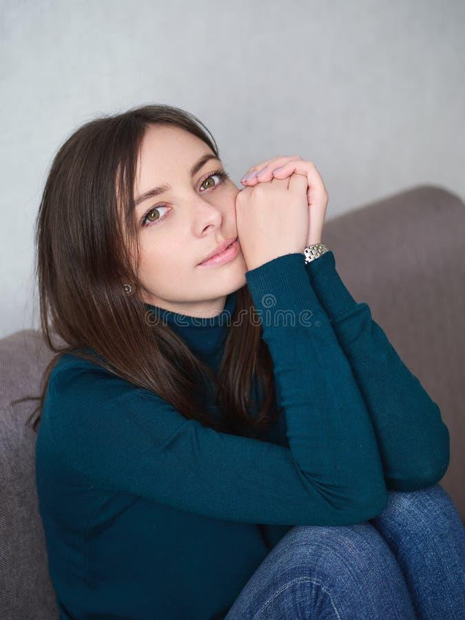 Милая женщина брюнета с великолепными глазами и прелестная улыбка в зеленом свитере и голубых джинсах подпирая вверх голову ослаб стоковое изображение