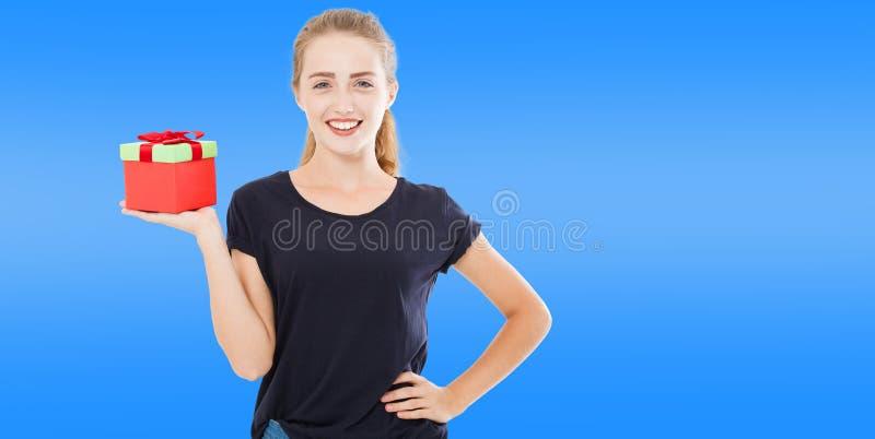 Милая женщина взрослого красиво в черной футболке держит подарок на голубой предпосылке Рождество, Новый Год и день рождения стоковое изображение