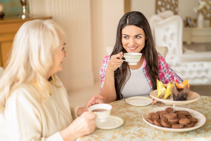 Милая женщина выпивает чай с ее старшей матерью на кафе стоковые изображения rf