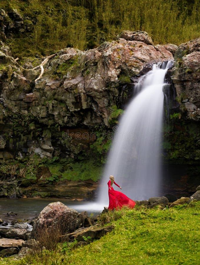 Милая женщина в длинном красном платье наслаждается влажным ветерком  стоковые изображения