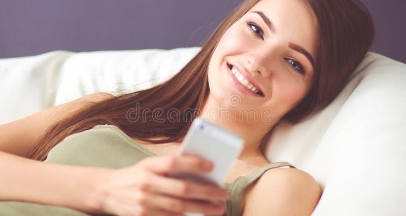 Милая женщина в ее живущей комнате лежа на кресле отправляя беспорядок стоковые изображения rf