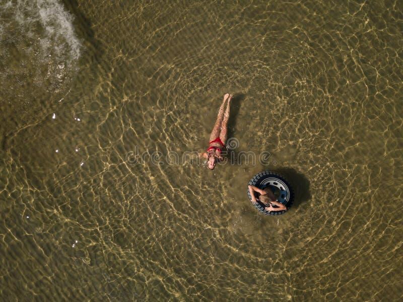 Милая женщина в красном купальнике бикини наслаждается водой моря, коричневого песка Вид с птичьего полета принятый трутнем стоковое изображение