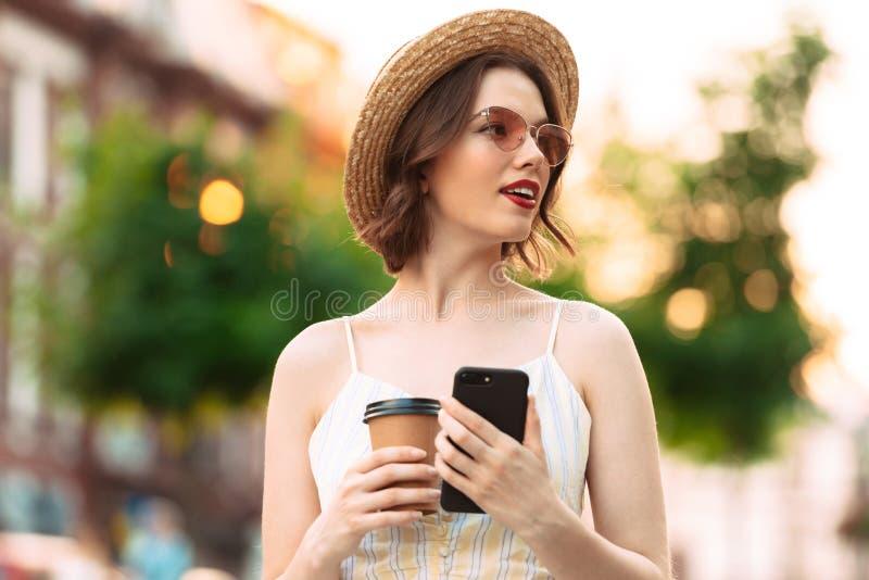 Милая женщина в представлять платья, соломенной шляпы и солнечных очков стоковые изображения
