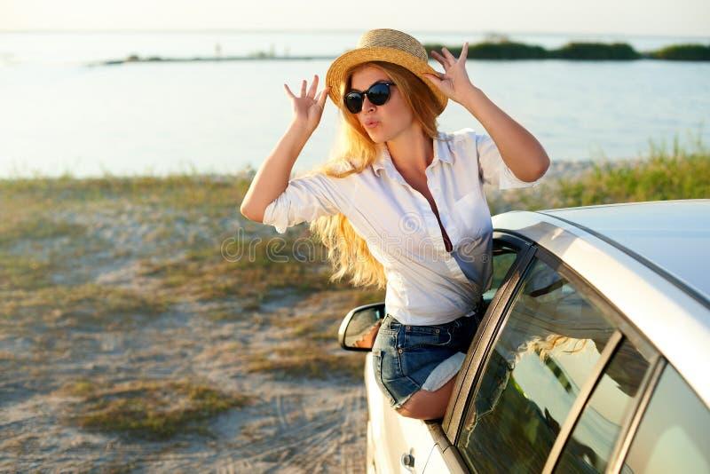 Милая женщина в соломенной шляпе наслаждаясь поездкой на летние отпуска Возбужденная молодая женщина поднимая ее руки автомобиля стоковая фотография rf