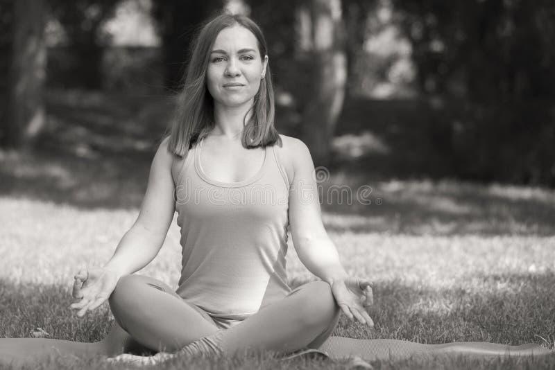 Милая женщина делая тренировки йоги в изображении парка черно-белом стоковые фото