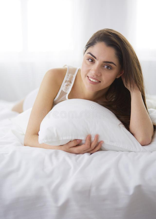 Милая женщина лежа вниз на ее кровати дома стоковые изображения rf