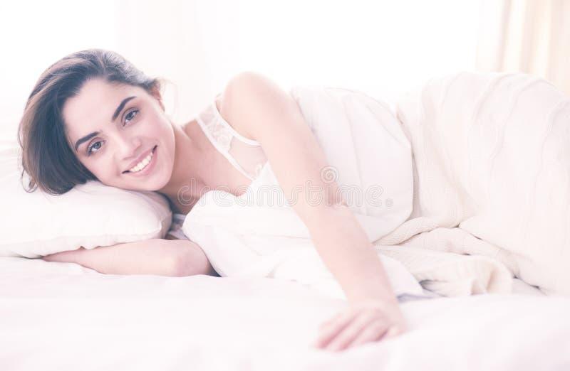 Милая женщина лежа вниз на ее кровати дома стоковое фото