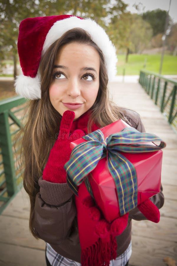 Милая женщина нося шлем Санты с обернутым подарком стоковые фото