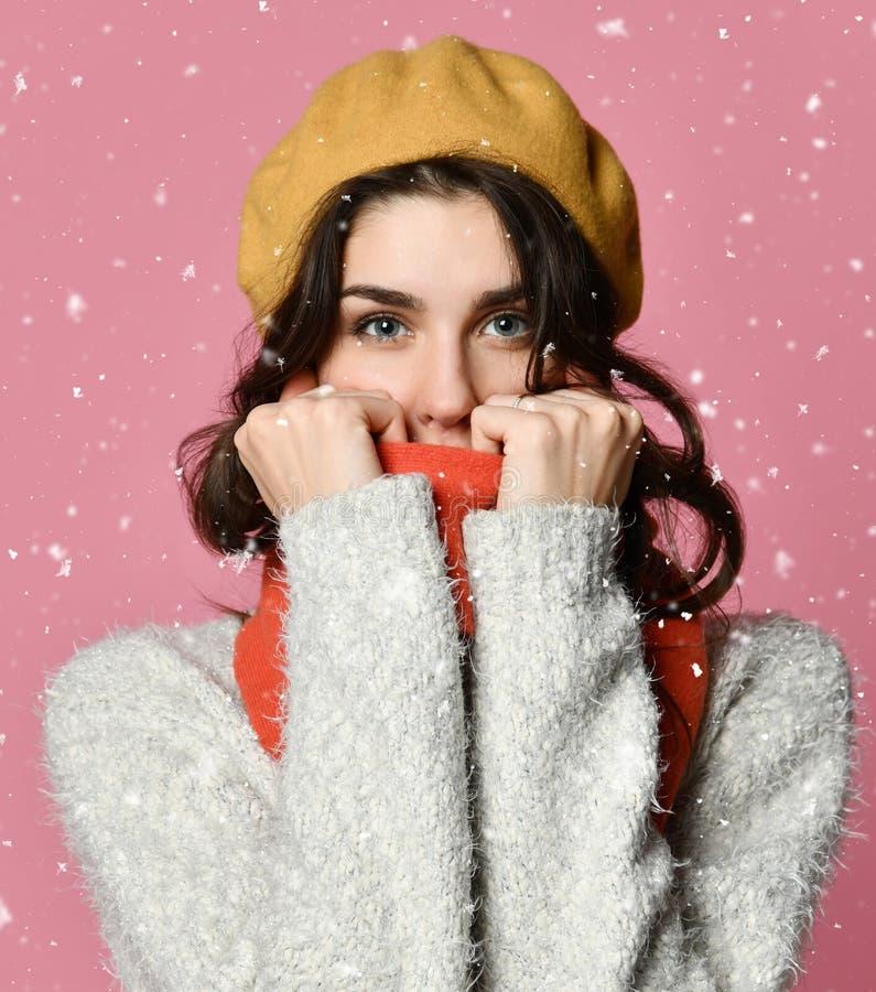 Милая женщина обернула вверх теплое в одеждах зимы стоковая фотография