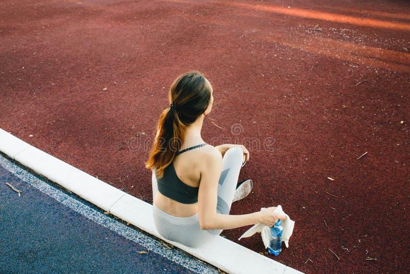 Милая женщина сидя на том основании с бутылкой воды после Jogging outdoors стоковое изображение rf