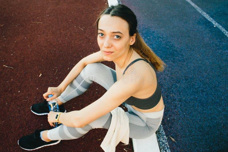 Милая женщина сидя на том основании с бутылкой воды после Jogging outdoors стоковое фото rf